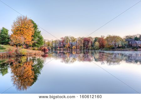 Sunrise on Braddock lake in Burke, Virginia, USA with reflection in autumn and orange tree
