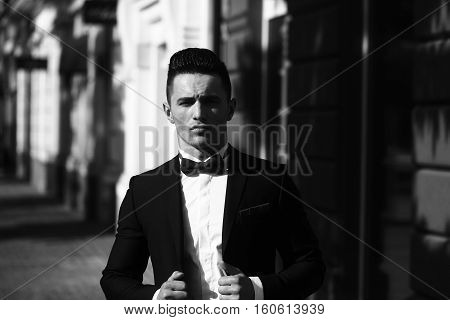 Young man wears suit and bow tie with confidence. Confident businessman black and white