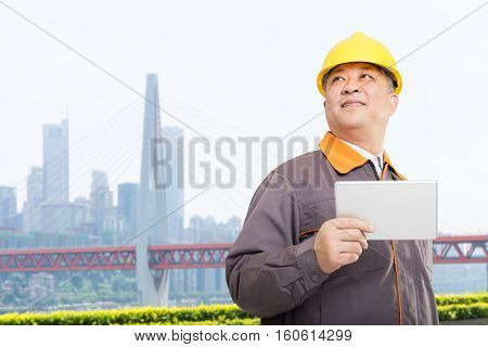 old asian man engineer with tablet and bridge in modern city