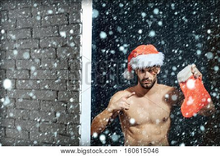 young handsome bearded sexy christmas surprised man with long beard in red santa claus hat and coat with muscular bare torso in xmas holiday holds new year stocking on white brick wall background