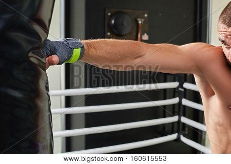 Young boxer training his skills hitting a punching bag. Train hard.