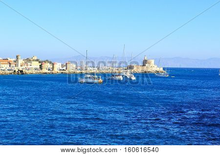 Bright blue sea with boats. Little tower on a bank