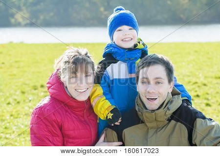 Outdoors happy family portrait of three cheerful people in park