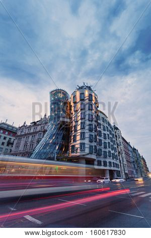 PRAGUE, CZECH REPUBLIC - JUNE 04, 2016: Modern architecture in Prague well known as Dancing house. Night view with passing cars and light stains of headlights