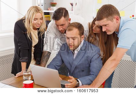 Successful team. Discuss internet strategy for company. Colleagues and coworkers look at laptop. Work and create together. Teamwork in modern digital business concept