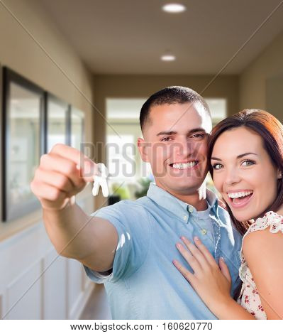 Happy Military Couple with House Keys Inside Hallway of New Home.