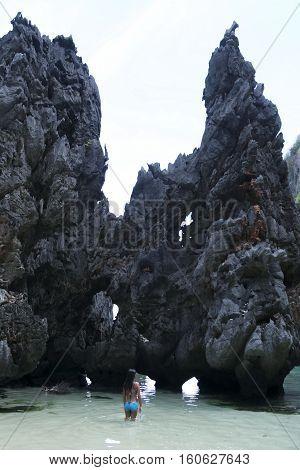 filipina woman exploring karst rock formations in hidden coastal lagoon of el nido in palawan the philippines