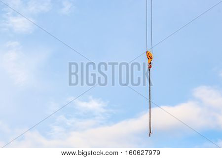 close up crane with a hook on the end in the blue sky background