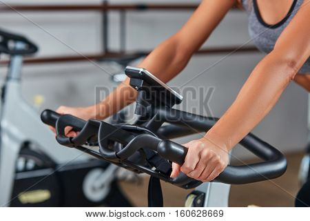 Strong female hand on a stationary bike in the gym