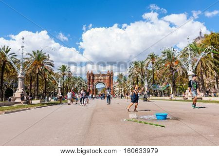 BARCELONA, SPAIN - SEPTEMBER 19; 2016; People strolling and enjoying sunny day outdoors on promenade by Arch of Triumph and children chasing soap bubbles in Barcelona Spain