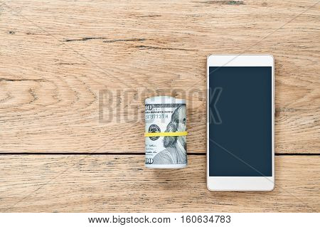 Roll of dollars tied with rubber band lying next to the phone on an old wooden table