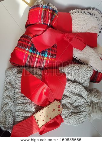 Close up view at Christmas gifts - colorful blankets and woolen winter hat with scarf wrapped in red ribbon