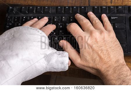 Young Man With Arm Cast Typing On A Keyboard