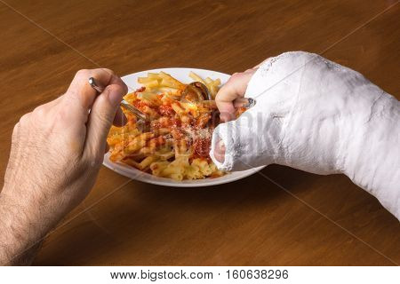Young Man In An Arm Cast Eating Pasta