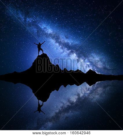 Milky Way. Night starry sky and silhouette of a standing happy man with raised up arms on the mountain peak near the lake with reflection in water. Blue milky way and man on the rock. Galaxy. Universe