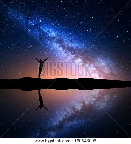 Milky Way. Night starry sky and silhouette of a standing woman with raised up arms on the hill near the lake with reflection in water. Colorful landscape with Milky Way and woman. Universe. Space