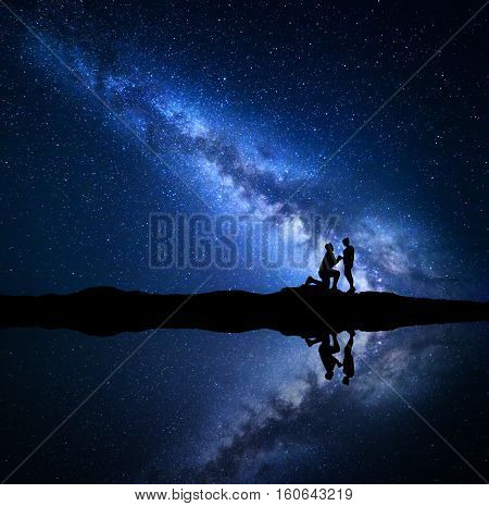 Milky Way. Silhouettes of a man making marriage proposal to his girlfriend on the mountain near the lake with starry sky reflection in water. Night landscape. Couple. Blue milky way with people. Space