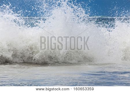 Large ocean waves with white foam. The raging ocean storm