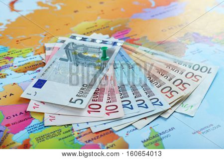 Euro banknotes fastened with push pin on world map background, closeup