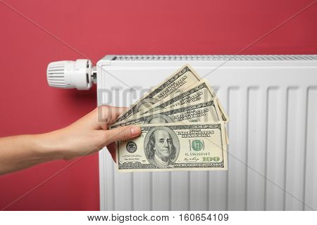 Female hand holding money near heating battery and pink wall