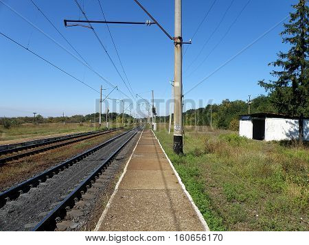 Double-track railway runs past the stopping point platform.