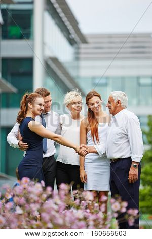 Businessman giving handshake to woman of a business team outdoors