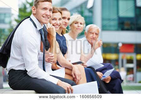 Successful business team with men and women sitting outdoors in front of the office