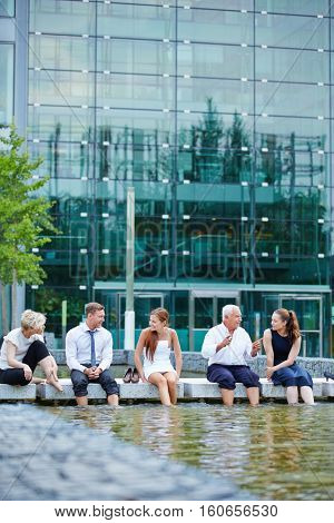 Relaxed business team having a meeting in summer with feet in water of a lake