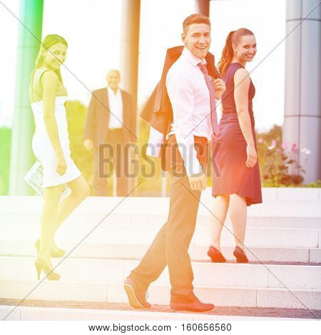 Young business people walking up stairs and turning around smiling
