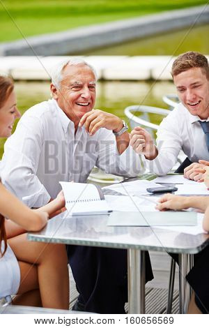 Communication in a business team during a meeting outdoors at a table
