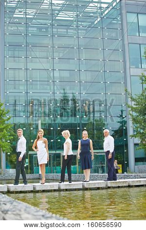 Business team standing in front of office building in summer