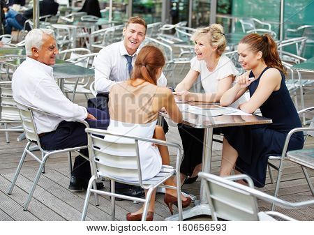 Smiling business people in team working in a coffee shop outdoors