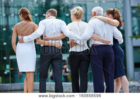 Group of business people embracing from behind and looking to office