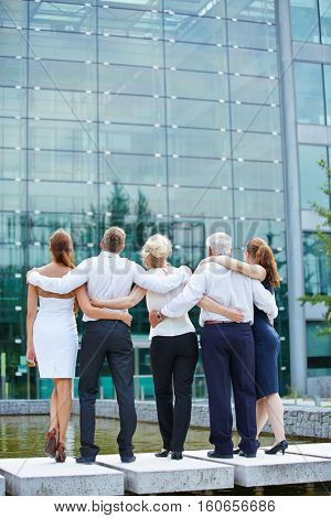 Business team from behind embracing and looking to office building