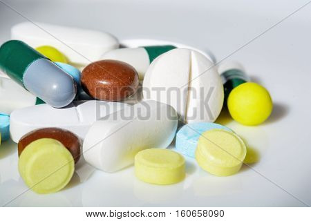 Tablets of different shapes, sizes and colors, close-up