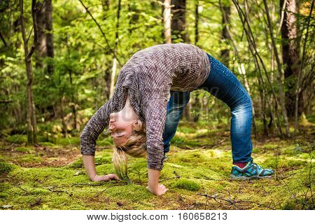 Young woman in back bend arch pose in mossy forest