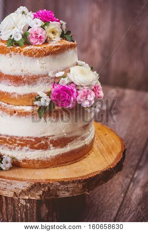 Wedding naked cake decorated with flowers on wooden cut stand, shot closeup
