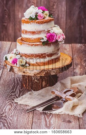 Homemade wedding naked cake decorated with flowers on wooden stand and serving set beside