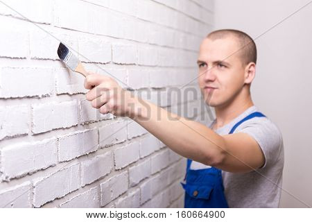 Young Handsome Man Painter In Workwear Painting Brick Wall With Paint Brush