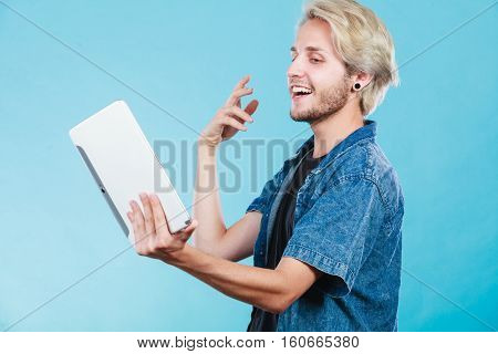 Education social media. Modern technology internet concept. Stylish handsome young guy using tablet computer on blue color