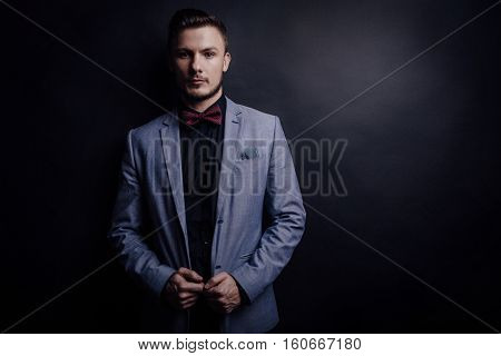 Portrait of handsome confident man in suit with butterfly looking forward on black background