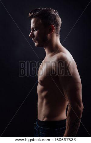 Portrait of handsome fitness man side view on dark background