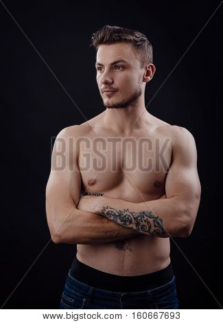 Image of handsome body guy with tatoo on arm on dark background