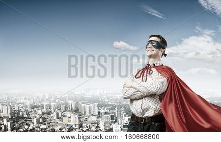 Young super hero man in mask with arms crossed on chest