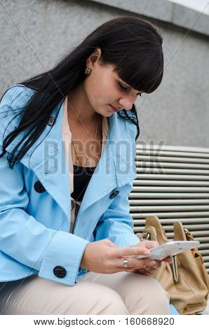 Dark Haired Girl Reading From A White Tablet