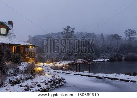 Fishing pond with fresh snow at daybreak in Cradle Mountain NP. A sign marks the start of the Enchanted Walk.