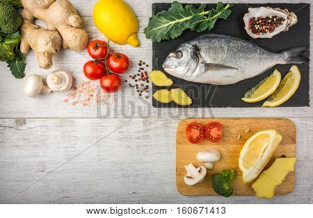 Useful dorado fish, rich in protein, vitamins, Omega 3 with vegetables, lemon and ginger, prepared for cooking on a white wooden table. Top view