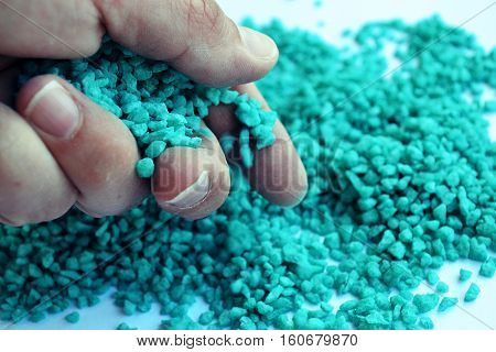 tiny blue pebbles being dropped out of a hand