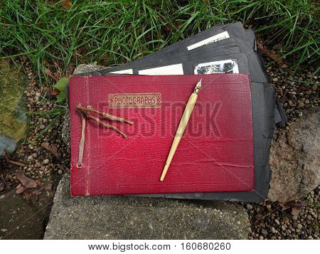 A vintage red leather album with the word, Photographs, printed on the cover is open enough to show the edges of black and white photos on black frayed paper.  A dip ink pen rests on top ready for writing precious names and dates before they are lost and
