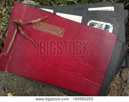 An old red leather family photo album with frayed cording and the word, Photographs, printed in gold opens slightly to show black paper pages with black and white photos.